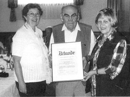 Jeho nástupkyně v roli pověřenkyň domovské rubriky krajanského časopisu Anni Scheuerová (vlevo) a Hilde Blauthová (vpravo) mu tady vroce 2006 předávají ocenění za dlouholetou činnost