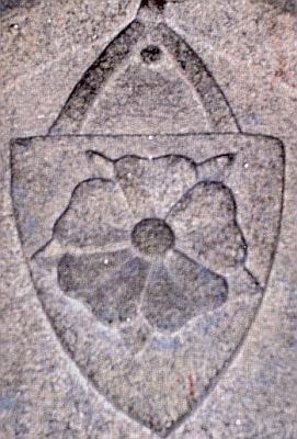 Na řemeni zavěšený gotický štít s rožmberskou růží nad vchodem do schodišťové věžice vyšebrodského klášter