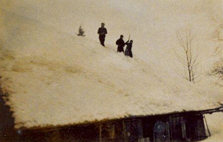 Odklízení sněhu ze střechy jedné z chalup na snímku z alba Traudl Gerardové, který byl pořízen o Vánocích válečného roku 1942