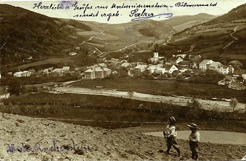 Na staré pohlednici Rejštejna je dominantní budova školy vlevo uprostřed u mostu přes Otavu
