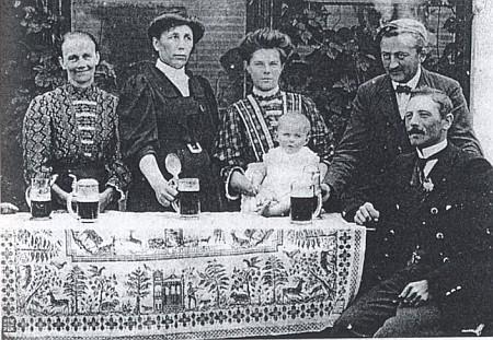 """Stojí tu vedle své první ženy Marie, zemřelé v roce 1912, s dcerkou Theresií, na stole s ubrusem zvaným """"Myslivcova svatba"""" (viz i Franz Höller)"""