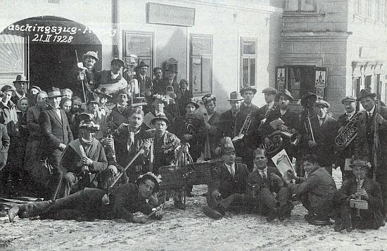 """Masopustní průvod z února 1928 před hospodou """"U čerta"""" v Hořicích na Šumavě"""