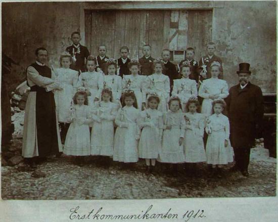 Stojí tu v cylindru, který nosil zřejmě i kvůli menší postavě, vedle dětí o jejich prvním svatém přijímání roku 1912 napravo, vlevo vidíme vyšebrodského cisterciáka pátera StanislavaPlonera