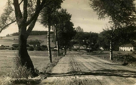 Pohlednice Johanna Mayera zachycuje Bližší Lhotu ze silnice do Horní Plané - tento úsek je dnes pod hladinou Lipenského jezera, vlevo mezi stromy vidíme budovu nádraží na původní železniční trati