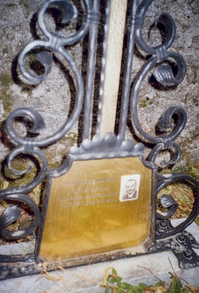 Detail náhrobního kříže v místě jeho posledního spočinutí při hřbitovní zdi kostela ve Svatém Tomáši a pamětní deska k uctění Bertlwieserových zásluh o renovaci kostela ve Svatém Tomáši na jeho venkovní zdi