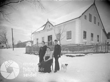 Dva snímky Bieblova domu v Houžné před zařízením obchodu pocházejí z roku 1922, na tom druhém přiběhl i pes
