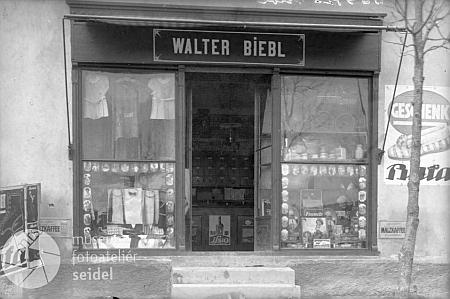 Jeho obchod se smíšeným zbožím na dvou snímcích z roku 1926