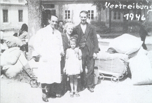 Tento snímek připojila ke své poznámce o výročí vyhnání v roce 1946: zachycuje vedoucího konzumu v Pohoří Theobalda Weißhäupla s jeho dcerkou, Mitzie Kastlovou a Adolfa Guschlbauera (Schustera) u zavazadel akočárků k odsunu