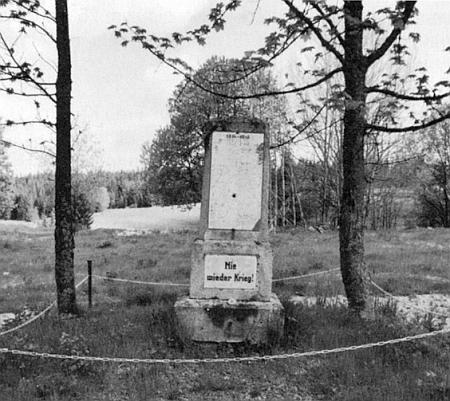 """Památník padlým v Pohoří na Šumavě s nápisem """"Už nikdy válku!"""", poškozený nahoře českým výstřelem a s horní částí zničenou - v místech za ním stávala zdejší škola"""