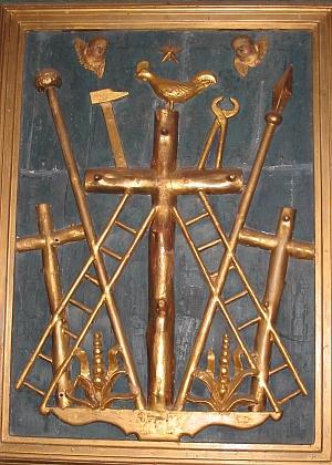 """Kohout, který podle Matoušova evangelia (25,75) dvakrát zakokrhal, když Petr třikrát zapřel Krista, na vrcholu kříže pod hvězdou zatmění na """"Arma Christi"""" zkostela Saint-Pierre ve francouzské obci Collonges-la-Rouge v regionu Limousin"""