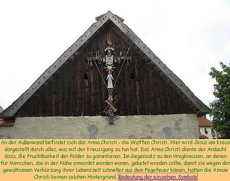 """Na štítě jednoho ze stavení """"selského muzea ve volné přírodě"""" Neusath-Perschen visí """"kohoutí kříž"""", provázený na webových stránkách obce Perschen v Horní Falci i výkladem jednotlivých symbolů """"Arma Christi"""" - účelem nebyla jako u polních křížů připomínka něčí časné smrti, nýbrž zaručení plodnosti polí názornou připomínkou zapřené oběti Kristovy"""
