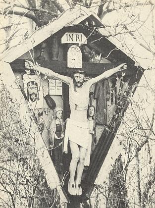 """I na tomto """"pašijovém kříži"""" (Passionskreuz) vbavorské vsi Ratzenleithen na severozápadě odPasova sedí kohout při hodinách, nastavených tu ovšem mylně na devátou místo na třetí"""