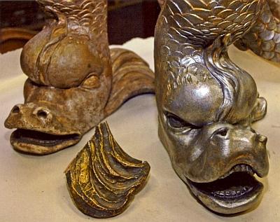 Detaily hlav delfínů na delfínovém kabinetu v průběhu jeho restaurování