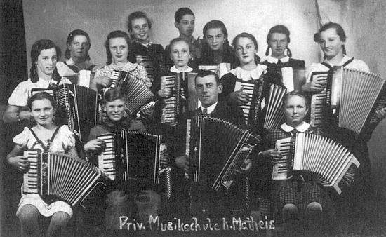 Stojí tu s harmonikou uprostřed druhé řady žáků a žaček soukromé hudební školy veválečném Krumlově roku 1941