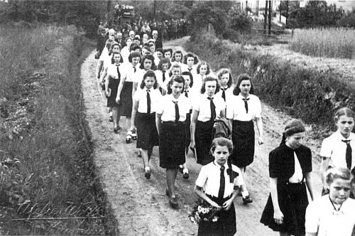 Při pohřbu ředitele krumlovského gymnázia Michaela Fernera roku 1944 kráčí tu ve druhé řadě uprostřed ve stejnokroji Svazu německých dívek (BDM) cestou k městskému hřbitovu (žně už začaly, jak vidno na poli při mezi)