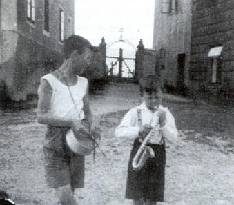 Vstup na hřbitov v Kapličkách mezi školou a farou, vepředu Tassilo a Günther Bitzanovi na snímku pořízeném jejich otcem 24. června roku 1935