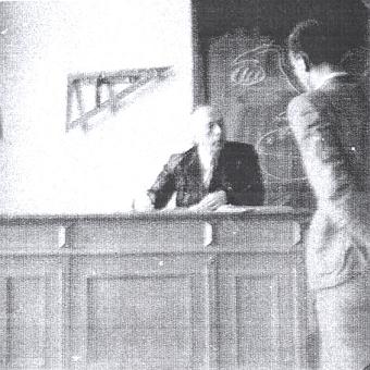 Sedí tu za katedrou jedné z tříd německé Oberschule für Jungen v České ulici někdy na konci školního roku 1940/1941, jak to zachytil amatérský snímek jeho tehdejšího žáka Tassilo Bitzana