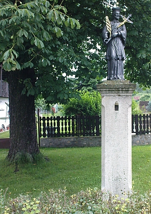 """U mostu přes Chvalšinský potok blízko domu řečeného """"Posthaus"""" stojí pilíř se sochou sv. Jana Nepomuckého, vlastně původní městský pranýř zroku 1690, stávající původně před zdejší radnicí aosazený bronzovou sochou v roce 1883"""