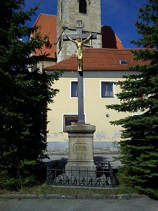 Za křížem s pozlacenou sochou Krista stojí chvalšinský gotický kostel sv. Maří Magdaleny snádhernýminteriérem