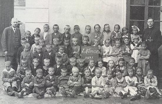 Prvňáci obecné školy v Kájově z roku 1931 a on, tehdy už sedmapadesátník, stojící nalevo při zdi školní budovy