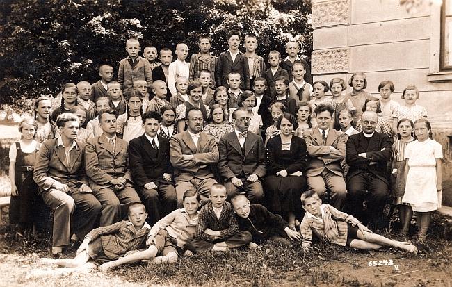 Na snímku se žáky a učiteli chvalšinské školy leží druhý zleva, nad ním sedí Karl Schläger