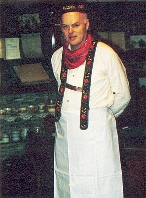 V někdejším kroji účastníka svatodušní jízdy svyšívanou čepičkou a šlemi kalhot k červenému šátku u krku, bílé košili a zástěře