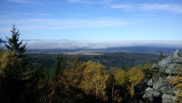 Pohled z Mandelsteinu - uprostřed pod podzimní inverzní oblačností je vidět Horní Stropnice, vlevo z mlhy vykukují vrcholky Slepičích hor