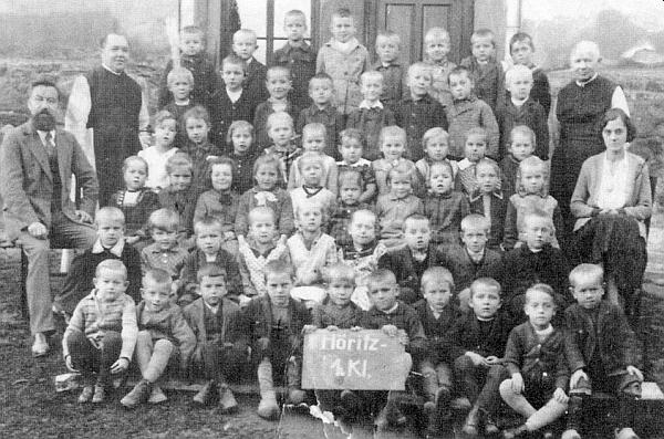 Tady je s žáky 1. třídy hořické obecné školy, ročník narození 1925, zachycen s narostlým plnovousem, za ním páter Odilo Petermichel, vpravo pak vikář páter Heinrich, oba cisterciáčtí řádoví kněží