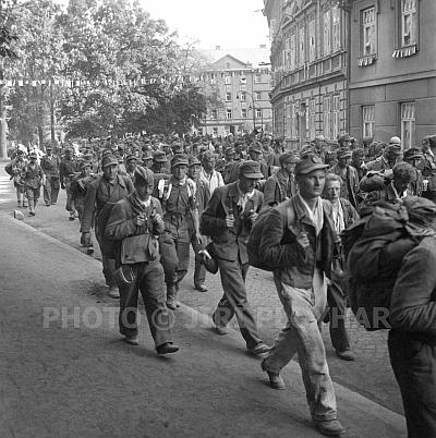 """Němečtí zajatci v květnových dnech roku 1945 kráčí jeho """"rodnou"""" ulicí Na Sadech, která nesla za války i jeho zásluhou nezapomenutelné označení """"Reinhard-Heydrich-Ring"""" (viz výše)"""