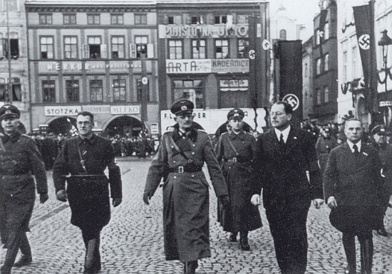 15. března 1939 tu kráčí před českobudějovickou radnicí, po jeho pravici generál von Weichs a Hans Westen, za nimi patrno zakrytí sochy Augusta Zátky drapérií s hákovým křížem