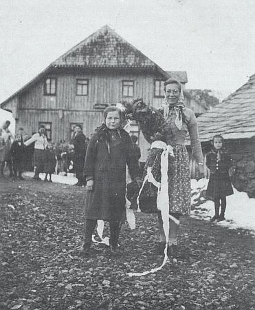 Stojí tu uprostřed při vázání věnce pro májku před Zanellovým hostincem v Bučině někdy za války