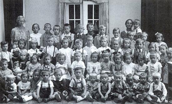 """Na dvou krumlovských školních fotografiích už po roce 1938 je zachycen na té s bosými kamarády v popředí stojící pátý zprava, na druhé s hošíkem v vlaječkou """"třetí říše"""" v prvé řadě je on ten ve třetí řadě docela nalevo zachycený žáček vedle dívenky s pannou"""