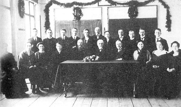 Učitelský sbor volarské obecné a měšťanské školy na snímku pořízeném roku 1925 u příležitosti rozloučení sředitelem Josefem Pexiderem, vedle něhož pátý zprava sedí Wenzel Draxler