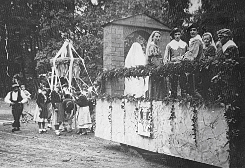 Dožínkový průvod s bystřickou mládeží kolem dožínkového věnce a s alegorickým vozem, na němž vpředu figuruje Bílá paní ze zámku