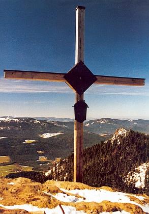 Kříž na vrcholu hory Ostrý, vpravo v pozadí vrchol Malého Ostrého