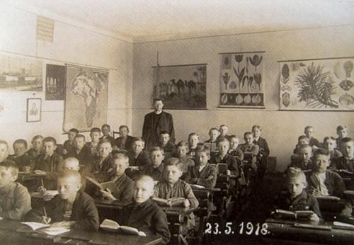 Datovaný snímek ho zachycuje jako katechetu mezi žáky, na nichž je patrna     nouze rakouského zázemí v posledních měsících první světové války