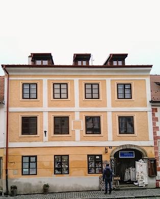 Pohlednice českokrumlovského nakladatele Eduarda Bayanda z roku 1910 zachycuje vpravo rodný dům čp. 48 v českokrumlovské Široké ulici (stojí před ním skupina lidí), nabarevném snímku je rodný dům dnes (2019)
