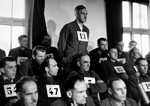 Stojící s číslem 13 mezi ostatními obžalovanými válečnými zločinci před americkým vojenským soudem v Dachau