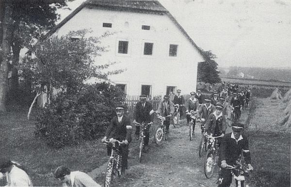 Na snímku z cyklistické slavnosti spolku Radsportverein Neuofen jede vepředu vlevo, za ním se bělá štít rodného domu v Nové Peci