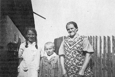 Stojí tu jako chlapec se svými sestrami před rodným stavením