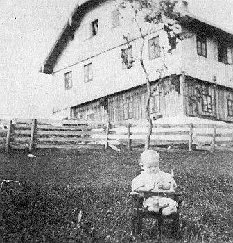 """Rodný dům zvaný """"ban Micheibauern"""" kolem roku 1910, před ním maličký ještě Kilian Fastner"""