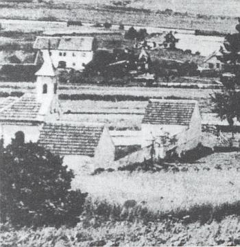 """Pohled od severu z pole nazývaného """"Joglquirchtn"""" nazápadní stranu """"nového"""" hřbitova vDolní Vltavici sdomkem na nářadí hrobníkovo, hřbitovní kaplí amárnicí"""