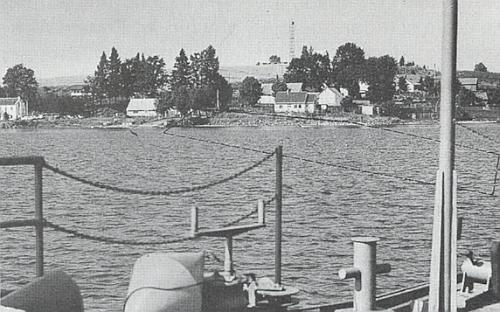 Zbylá zástavba někdejší Dolní Vltavice s černou čarou na ploše hladiny přehradního jezera (snímek je pořízen z lodi), vyznačující průběhem zatopené obvodové zdi polohu někdejšího hřbitova