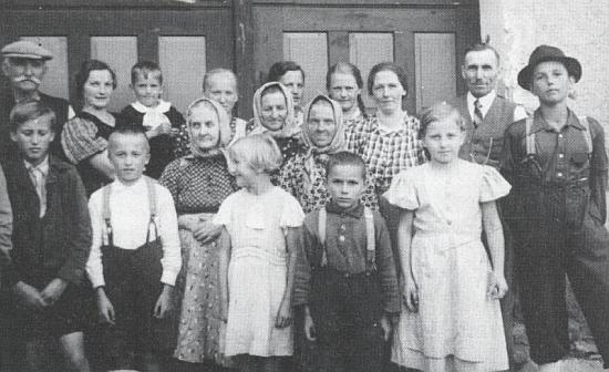 Rodina Fidlerova s čeledí před branou do dvora mlýna na snímku z roku 1939