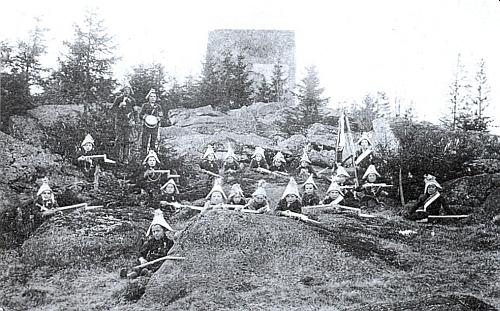 """Žáci nově zřízené školy ve Svatém Tomáši tu na snímku z roku 1905 """"brání"""" Vítkův kámen"""
