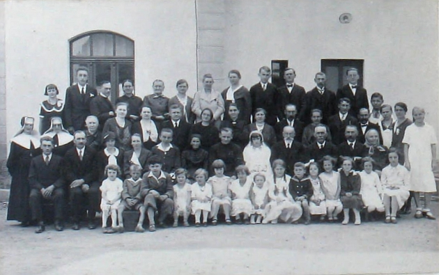 """Na snímku z jeho primice v rodné Železné roku 1934 sedí uprostřed mezi maminkou a sestřičkou Mariechen, která tu figuruje v roli """"Primizbraut"""", tj. """"primiční nevěsty"""""""
