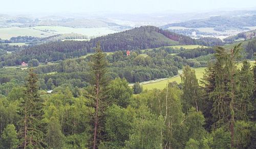 Vrch Raciberk s raně středověkým hradištěm na vrcholu, v popředí návrší Olymp s vyčnívající věží kostela sv. Mikuláše v Boleticích