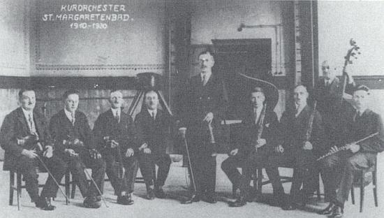 """""""Badhausorchestr"""" Lázní sv. Markéty, s uprostřed stojícím prachatickým školním řídícím Viktorem Ernstem Zimmerem, je zachycen na snímku z roku 1920, kdy slavil 10 let svého trvání"""