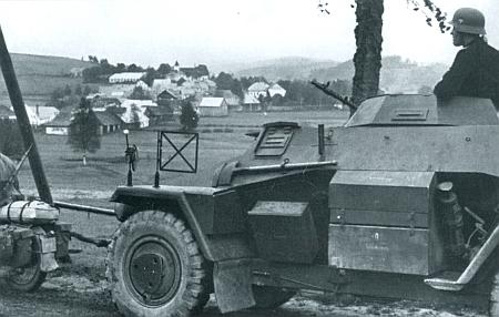 """Tady tvoří Kunžvart se svým kostelem pozadí snímku, zachycujícího v nacistické propagační publikaci """"kolonu průzkumných obrněných vozidel"""" wehrmachtu v říjnu 1938 na dohled od obce"""