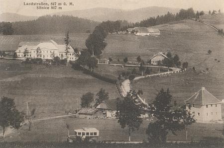 Zaniklá osada Silnice na staré pohlednici s velkou budovou nalevo, která sloužila jako celnice i hotel